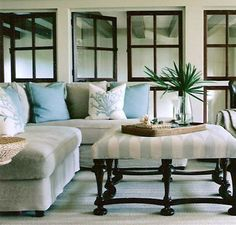 Coral pillows and a subtle striped ottoman creates an inviting living space inspired by the sea.