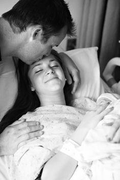 hombre besando en la frente a una mujer que acaba de dar a luz