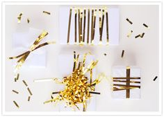 Add some sparkle: There are few things in this world more festive than gold tinsel. There are a whole bunch of ideas here, but they all boil down to some version of this: buy one of those gold fringe door curtain at a party store; destroy it; and glue/tie/tape the pieces to your presents in random but attractive configurations.