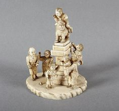 OKIMONO, Elfenbein, um eine Statue mit einem Kilin mehrere spielende Kinder und ein Mann, H 12, besch., rest., am Boden Ritzsignatur auf eingelegtem Rotlackplättchen, JAPAN, Meiji-Zeit
