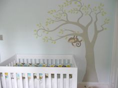 The crib bedding in chocolate, butter yellow and robin's egg blue sets the color scheme in this modern, gender neutral nursery. The wall is painted a tranquil shade of blue. A hand-painted wall mural like this one with a monkey in a tree is a darling way to incorporate nature into your design. Your little one will love it too!