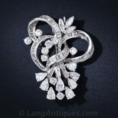 Platinum Diamond Pendant Brooch c. 1950's - 50-91-139 - Lang Antiques. Undulating ribbons of baguette-cut diamonds cinch a sparkling bouquet of bright white pear shape, round, and marquise-cut diamonds set in platinum for a glamorous and impressive effect. This stunning pin and pendant contains 7.50 carats total diamond weight and measures 1 3/4 inches tall by 1 5/16 inches in width. Quintessentially fabulous 50's!