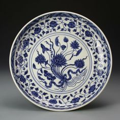 China, Ming Period, blue and white charger, painted with bands of floral and lotus motifs, key fret pattern, and a central decoration of a gathered bouquet. Diameter 13 in.