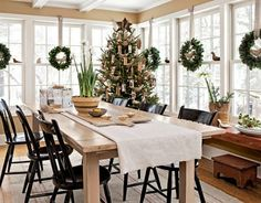 What a great table for gift wrapping! I love the wreaths and the casual elegance of this room. So bright and inviting!