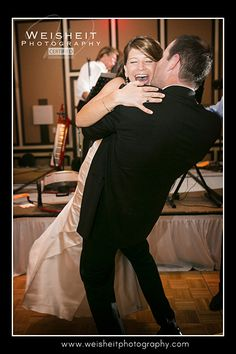The hem of a laughing bride's ivory satin trumpet style dress floats above the floor as her new husband lifts her into the air and kisses her on the cheek. The stunning couple, who held their wedding reception at the PGA National Resort and Spa in Palm Beach Gardens, were dancing to the music of the John Parker Band, premier south Florida wedding entertainers! http://www.jpband.com/weddings/