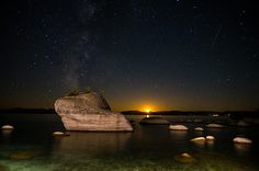 The moon setting and Milky Way behind Bonsai rock along the eastern shores of Lake Tahoe, Nevada.