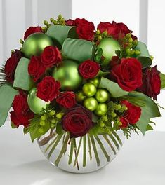 Bring the joy and good tidings of the holiday season straight to the door. Bursting with bright seasonal color, this bouquet boasts both red roses and spray roses whimsically accented with green hypericum berries, green glass holiday balls and green taffeta ribbon, artfully arranged in a clear glass bubble bowl vase.