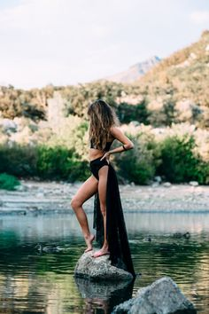 Woman in Black Two Piece Bikini Standing on the Gray Rock on the Body of Water during Daytime