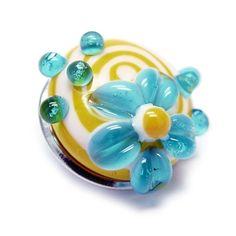 Alexiss Glas Button - gelber Druckknopf mit weißen Streifen und blauer Blüte
