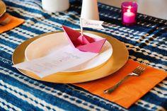 mesa posta com barco de papel de dobradura cor de rosa, usado como marcador de lugar.