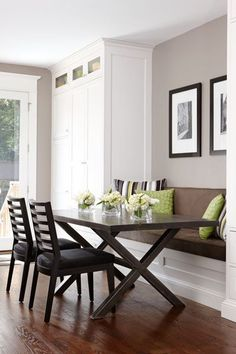 A built-in banquette flanked by tall pantry cabinets creates an eating nook. Dark-stained oak floors help warm up the white cabinetry.