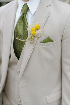 Tan suit with a green tie and pocket square are livened up with a yellow button boutonniere