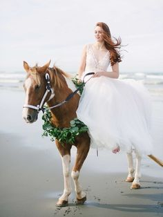 Bride Riding a Horse on a Beach     Photography: Blue Rose Photography. Read More:  http://www.insideweddings.com/weddings/rustic-understated-coastal-styled-shoot-with-muted-blue-palette/773/
