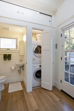 small laundry room (closet) inside of a bathroom - clean, white, efficient, lots of natural light
