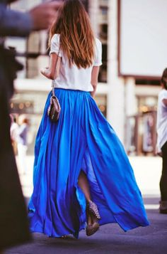 Gorgeous white haf sleeveless blouse with stylish blue long maxi skirt and high heels pumps