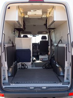 Functional interior of Miguel's Sprinter van moto hauler, with flip-down bunk beds, and open and closed overhead cabinets.