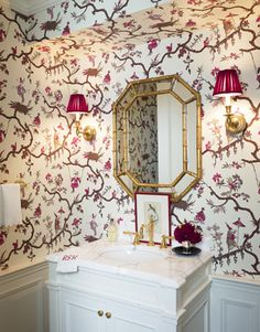 Designer Ashley Whittaker replaced clinical ceiling-high white tile with fanciful Asian-themed wallpaper (lampshades mimic the red parasols) and a faux-bamboo mirror.   - HouseBeautiful.com