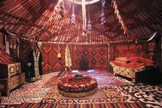 Brightly colored carpets adorn the floor and interior walls of a yurt, a domed tent used by nomads