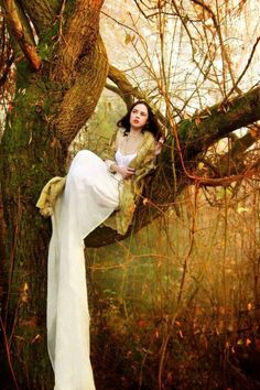Girl wearing a white gown sitting on a tree branch outside