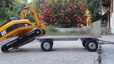 RC Bruder Cat 319D LN climbing onto Tractor