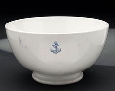 Government issued, earthenware mess bowl as used by ratings. It is white with a small foul anchor in blue, printed on one side near the top. This type was discontinued in 1926.