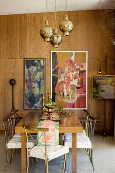 Dining room -  managed to update mid-century paneling! - abstract paintings, brass chairs