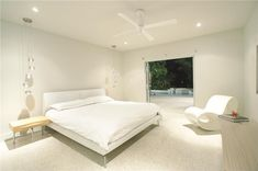 Bright white modern master bedroom with hanging lights