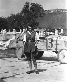 """Aloha Wanderwell, our """"Queen of Adventure"""", with #3 Model T Ford in the back ground and a still camera in her hand. Aloha has already driven with the Walter & Wanderwell Expedition almost around the world. 1929 in Beijing."""