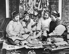Chinese women playing a game together; 1900.