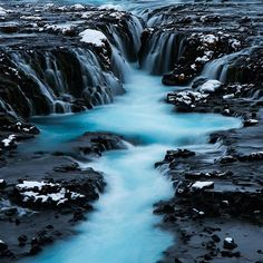 An electric blue vein of water runs through the deep black volcanic rocky abyss of Bruarfoss #MyStopover