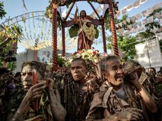 Filipino devotees covered in mud and dried leaves carry an image of Saint John the Baptist during a procession in a pagan religious tradition to mark the 'Taong Putik' (Mud People) festival and the Feast of Saint John the Baptist in the village of Bibiclat, Aliaga township in Nueva Ecija province