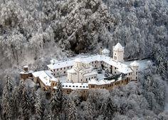 Manastirea Tismana.   Intr-un peisaj fermecător, asemenea unui castel medieval cu bastioane la colţuri, Mănăstirea Tismana este aşezată pe vârf de stâncă, pe muntele Stârmina, înconjurată de culmi împădurite şi stâncoase, lângă gura întunecată a Peşterii Sfântului Nicodim şi de sub ale cărei ziduri ţâşneşte apa, rostogolindu-se în cascadă, cu o cădere de cca 40 m în râul Tismana.
