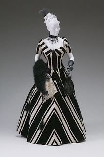 """By the 1890s the Victorian Dress becomes similar to a power suit in today's world. The bodice was a tight form fitting jacket. Sleeves do begin to develop more. This time in fashion women begin to show """"masculine"""" strength in clothing."""