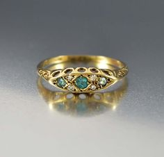 Hailing from England, this lovely antique wedding band ring features an oval front with emerald gemstones and sparkling diamonds. The gemstones are raised with a pierced design work and a scrolling en