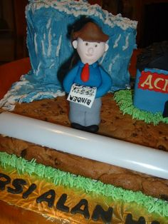 """This was part of the cookie that I decorated for my boss' 40th anniversary in business.  I baked the cookie on a cookie sheet. I covered the name of the biz.  This is an insurance disaster cake.  The wave in back was made out of RKTs (note to self to let it dry b/4 putting B/C on it.  Lots of skewers & a dowel in there. The building was also RKTs & Alan, the truck & tree were fondant. He is holding a binder which is a temporary insurance policy.  I call this cake """"Hazard? What Hazard?"""""""