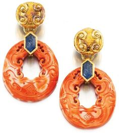 Pair of coral and sapphire ear clips, David Webb.     Each suspending a carved coral hoop from a surmount highlighted with an engraved sapphire, signed Webb.  Sotheby's.