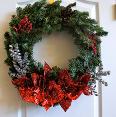 Festive Christmas holiday wreath, red glitter poinsettias, holly berries, evergreen