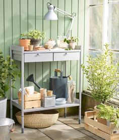 A gray potting bench filled with plant pots and cuttings.