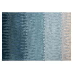 Acaica teppe fra Linie Design. Et håndtuftet teppe i blåtoner. Med stilrene grafiske m...