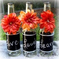 These are recycled beer bottles made into wonderful centerpieces for any occasion! They are made with simple fall color flowers accented with a gold rinestone. Sheer and cream ribbon also give it a pop!     They are also painted in chalkboard paint, so you can write what you please on them with chalk!  Very creative twist on a simple bottle :]...