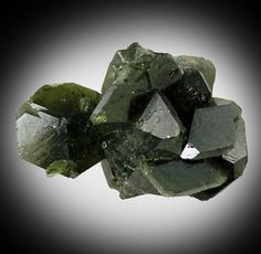 Dark Green Uvite Cluster.  Uvite is an uncommon form of Tourmaline, and it forms different crystal formations than the most of the other Tourmalines. Though it lacks the color diversity as some of the other Tourmaline forms, it does occur in beautiful green and reddish-brown crystals, as well as lustrous submetallic crystals.