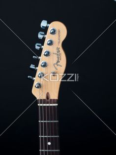 headstock of guitar against dark background. - Close-up cropped image of peghead against dark background.
