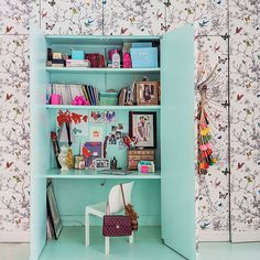 Home office within an eggshell cupboard, with statement wallpaper