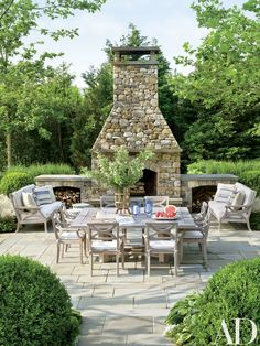Arranged near the outdoor fireplace are Country Casual sofas and chairs cushioned in a Sunbrella fabric.