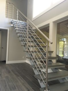 """This floating straight stair is prime example of our architectural charm, which delivers the combination of a welded aluminum straight stair in powder coated anodized silver with a custom machined stainless steel railing, matched with 2"""" thick stained hard maple tread. These materials combined create a truly unique, contemporary, and elegant stairway. Contact Superior Spiral Stairs today and allow us to make your dreams come true! www.superiorspiralstairs.com (941) 922-8846"""