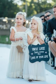 "Ivory flower girl dress idea - flower girls in ivory gowns carrying sign that reads ""Here comes the love of your life"" {Bradley Images, Inc.}"