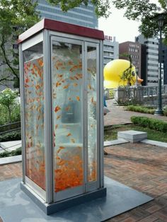 "Fish Tank Phone Booth - Rose Garden, Nakanoshima Park, Osaka, Japan. art installation, part of Aqua Metropolis Osaka 2011 Festival (promoting healthy waterways & environmentally-friendly practices). photo by Otaku Subreddit || **NOTE** the duck in the background is from the world wide ""Rubber Duck"" art project by Dutch artist Florentijn Hofman: http://www.florentijnhofman.nl/dev/project.php?id=154"