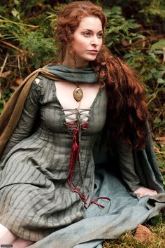 Very cool cape, and I like the lace-up detailing on her sleeves.