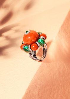 Der Ring Flamboyant aus Platin ist besetzt mit einer 30,90 karätigen Korallenkugel, mit je vier Korallen- und Smaragdkugeln, Onyx und Brillanten