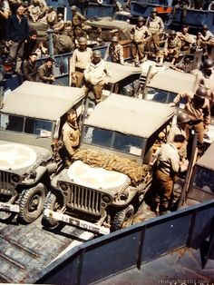 Trucks and jeeps which will carry men and supplies to the front lines of the invasion are loaded onto an American Landing Craft in a British...